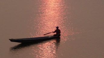 Ein Fischer fährt in Vientiane (Laos) auf dem Mekong durch die Abendsonne.